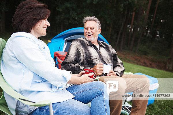 Ein erwachsenes Paar sitzt auf Campingstühlen  neben dem Zelt  hält Tassen Tee und lächelt