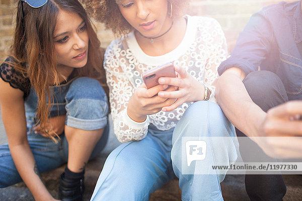 Drei Freunde sitzen auf der Straße und schauen auf ein Smartphone