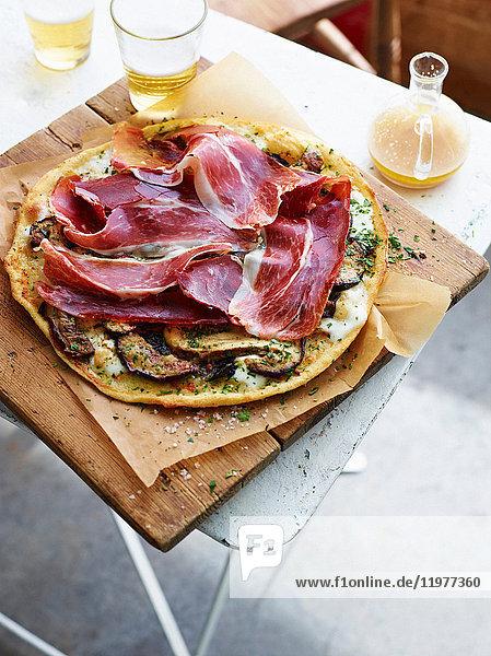 Steinpilz- und Prosciutto-Pizza auf Servierbrett  erhöhte Ansicht