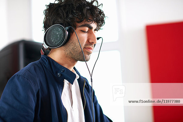 Junger männlicher College-DJ-Student hört Musik über Kopfhörer