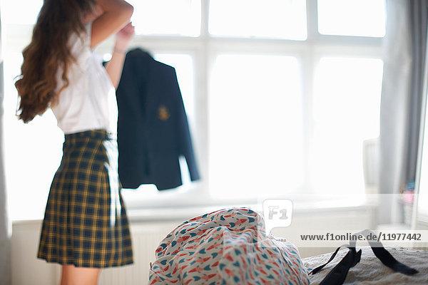 Teenage schoolgirl styling long hair in bedroom