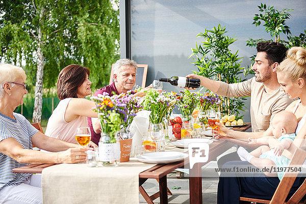 Eine Drei-Generationen-Familie isst zu Mittag und schenkt Wein auf dem Terrassentisch ein