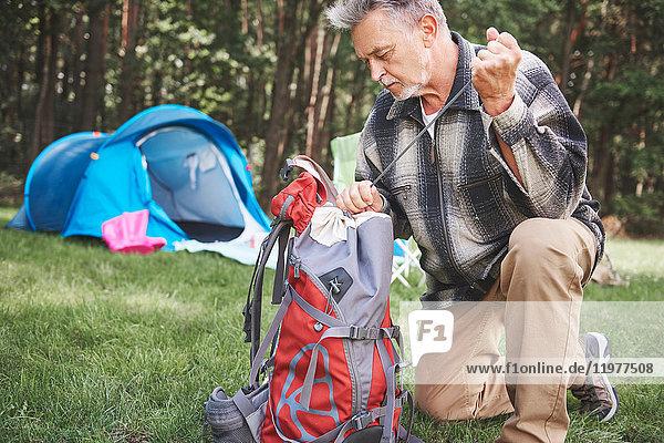 Älterer Mann neben Zelt  Rucksack packen