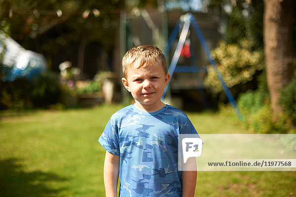 Porträt eines süßen Jungen im Garten stehend
