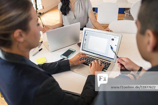 Geschäftsfrau tippt bei Konferenztisch-Sitzung am Laptop