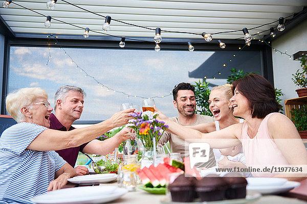 Drei-Generationen-Familie macht einen Wein-Toast beim Mittagessen auf der Terrasse