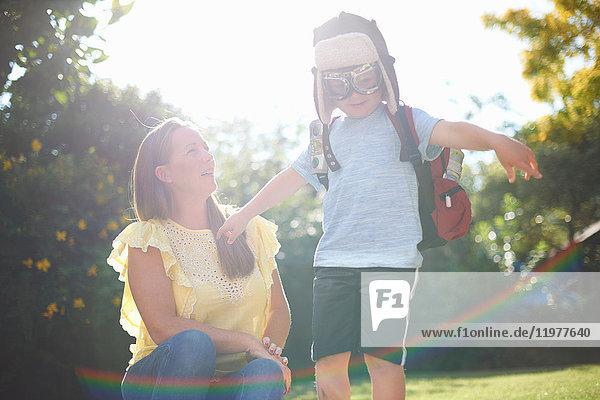 Reife Frau mit Sohn  die mit offenen Armen im sonnenbeschienenen Garten vorgibt  Pilot zu sein