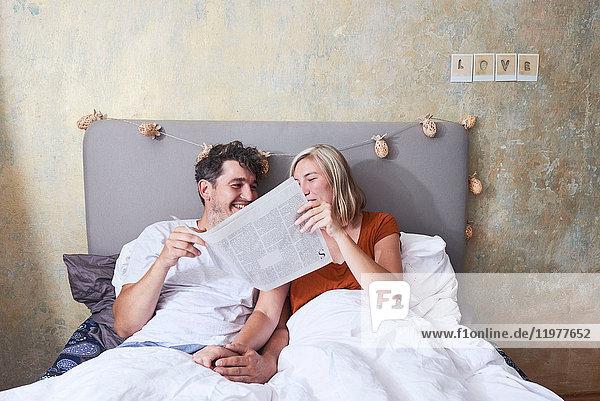 Paar im Bett  Händchen haltend  Zeitung austauschen