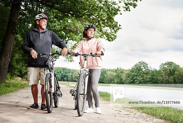 Ein erwachsenes Paar  das mit Fahrrädern auf einem ländlichen Pfad geht und die Aussicht betrachtet