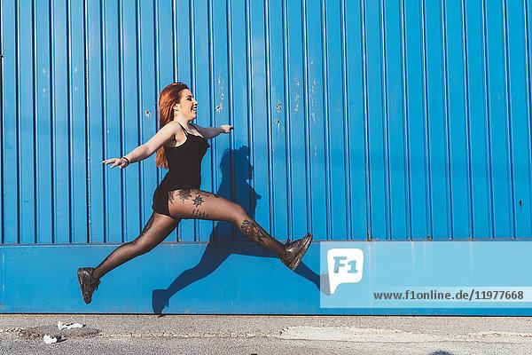 Frau vor blauer Wand springt in die Luft