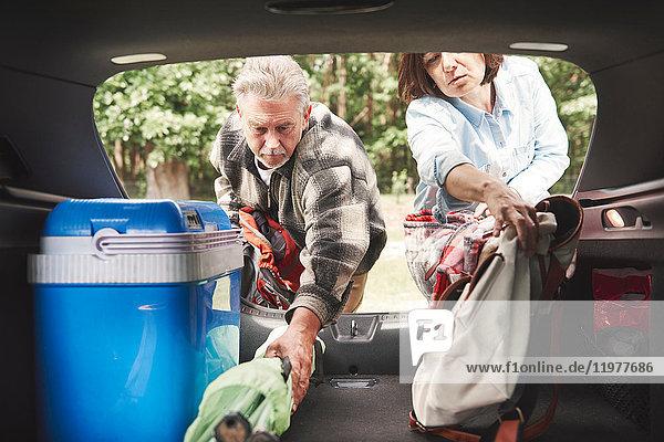 Erwachsenes Paar entfernt Campingausrüstung aus dem Kofferraum
