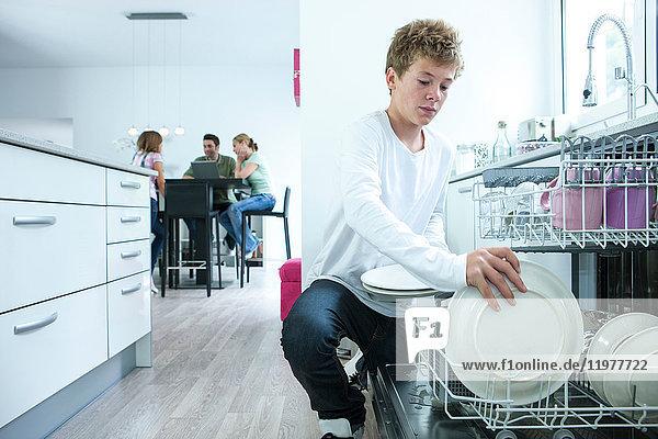 Teenager entfernt Teller aus dem Geschirrspüler in der Küche