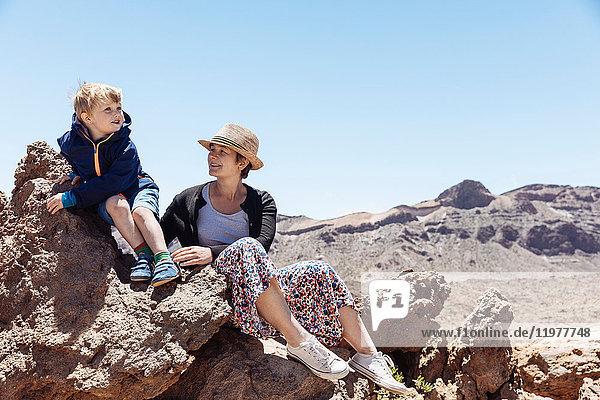 Junge und Mutter sitzen auf Felsen am Teide  Teneriffa  Kanarische Inseln