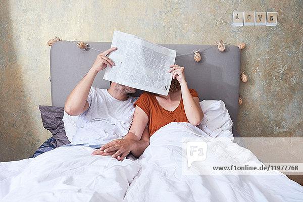 Paar im Bett  Hände haltend  Zeitung vor das Gesicht haltend