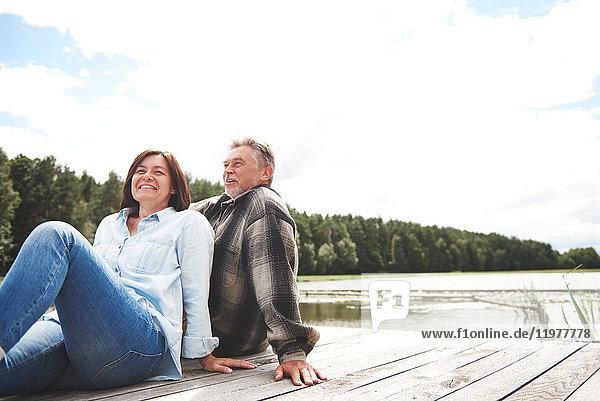 Älteres Paar entspannt sich auf einem Steg am See