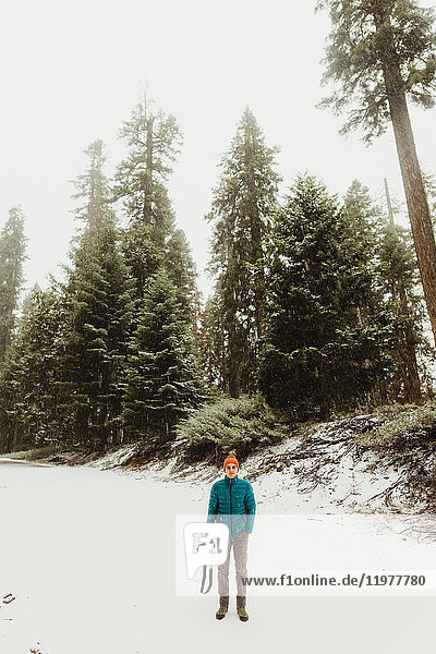 Portrait of young man holding camera in snowy forest  Sequoia National Park  California  USA