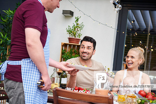 Mann übergibt Teller an Paar mit kleiner Tochter beim Familienessen auf der Terrasse