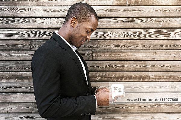 Mann benutzt Mobiltelefon durch Holzverkleidung