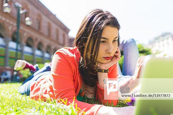 Frau im Stadturlaub mit Laptop auf Rasen  Mailand  Italien