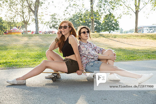 Portrait of two young women outdoors  sitting on skateboard