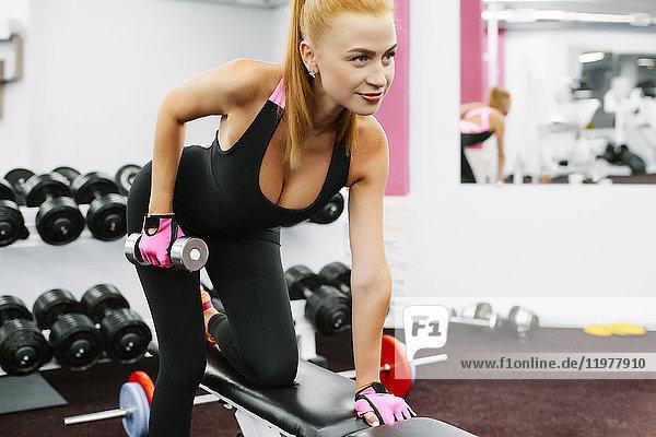 Frau in Turnhalle mit Kurzhanteln