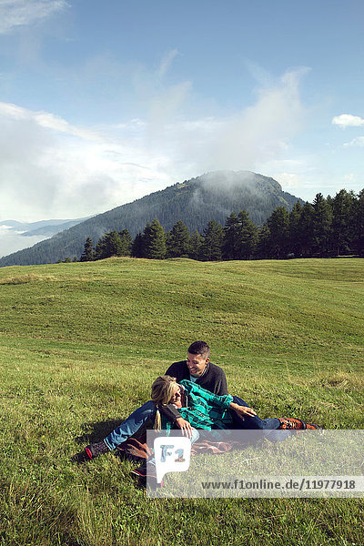 Couple lying down relaxing in field landscape  Tirol  Steiermark  Austria  Europe