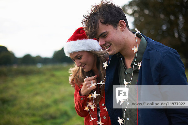 Young couple in santa hat and xmas light garland strolling in field