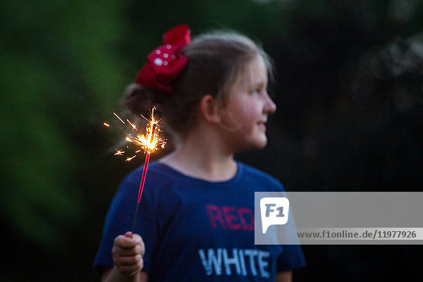 Girl looking away while holding sparkler at night on independence day  USA