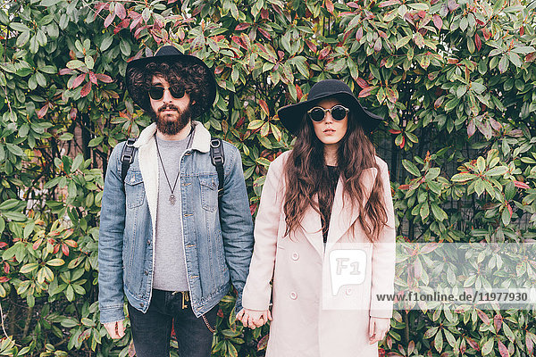 Portrait of young couple  wearing hats and sunglasses  holding hands