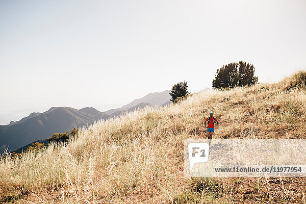 Man running outdoors in rural  hilly setting  Santa Barbara  California  USA