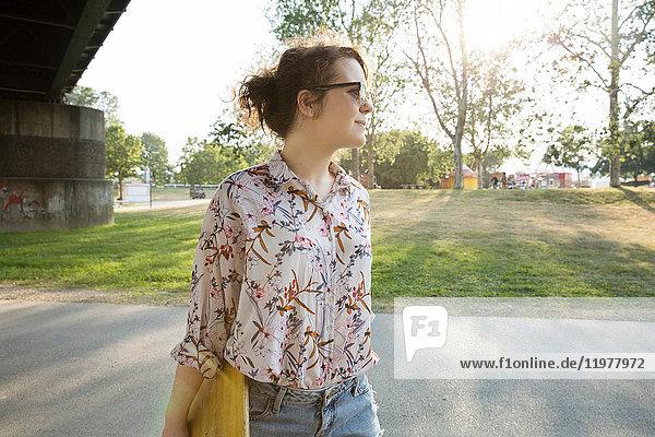 Junge Frau  die im Freien geht und ein Skateboard trägt