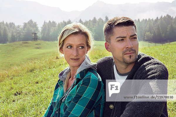 Portrait of couple in field landscape looking away  Tirol  Steiermark  Austria  Europe