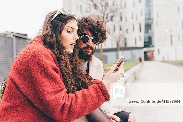 Young couple sitting outdoors  looking at smartphone