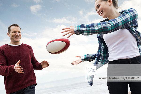 Vater und Tochter spielen Rugby am Strand