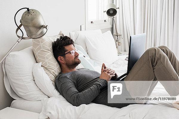Mittelgroßer erwachsener Mann im Bett liegend,  mit Laptop