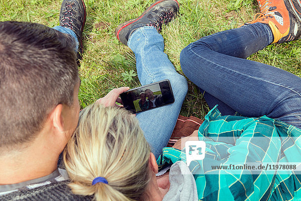 High angle view of couple sitting on grass taking selfie