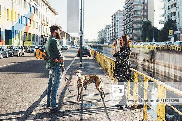 Junge Frau fotografiert Freund und Hund am Kanal mit Sofortbildkamera Junge Frau fotografiert Freund und Hund am Kanal mit Sofortbildkamera