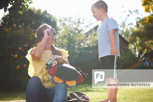 Mature woman with son putting on pilot goggles in garden
