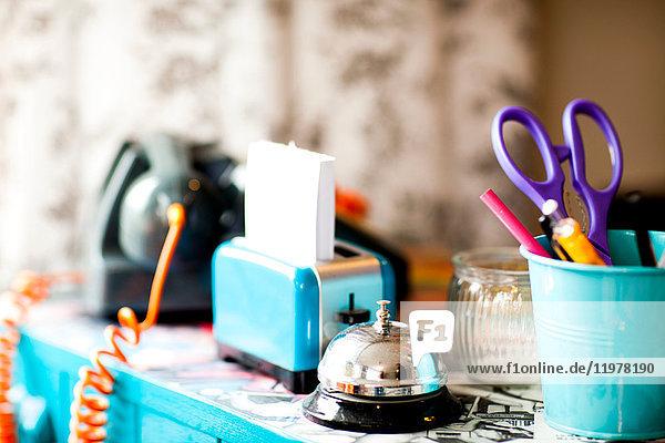 Schreibwaren und Serviceglocke am Empfangstresen eines skurrilen Friseursalons