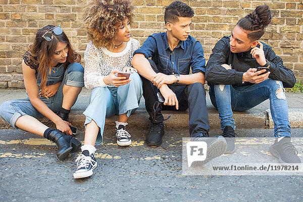 Vier Freunde sitzen auf der Straße und schauen auf Smartphones