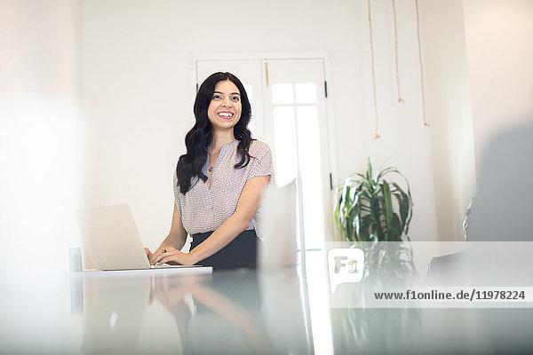 Junge Geschäftsfrau tippt am Schreibtisch am Laptop