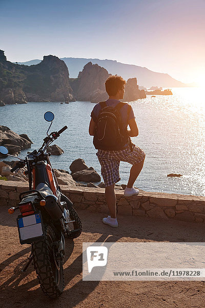 Man with motorbike looking away at view of sunset over sea  Olbia  Sardinia  Italy
