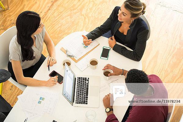 Draufsicht auf drei Geschäftsfrauen und -männer,  die sich am Bürotisch treffen