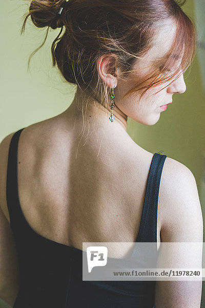 Rear view portrait of young woman looking over her shoulder
