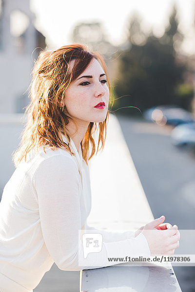 Portrait of beautiful young woman looking out from balcony on sunlit roof terrace