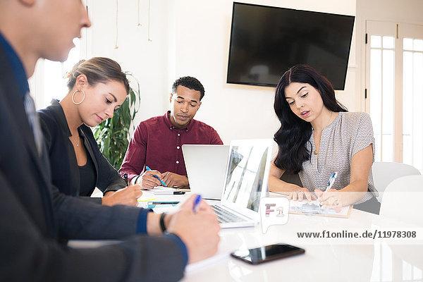 Junge Geschäftsmänner und -frauen machen Notizen am Vorstandstisch