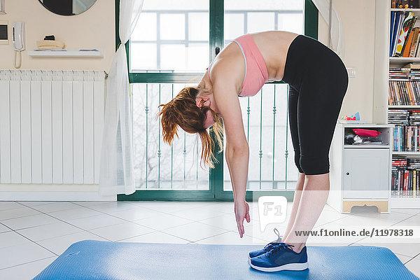 Young woman practicing yoga bending forward on yoga mat