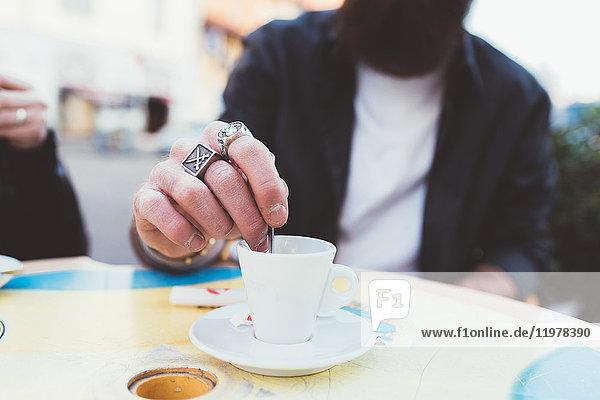 Ausschnitt eines Mannes  der Kaffee rührt