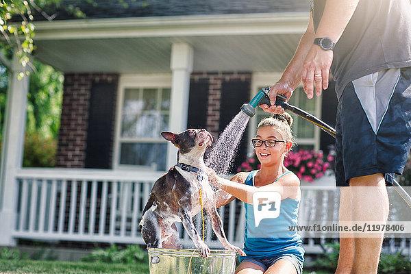 Vater und Tochter waschen Hund mit Schlauch