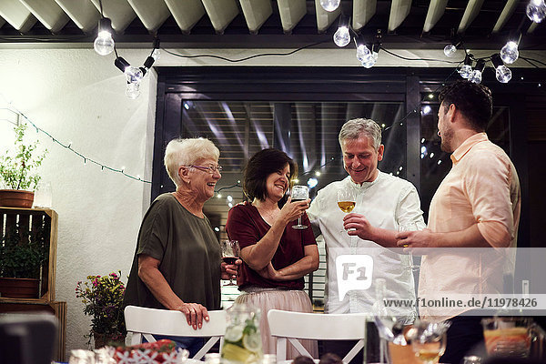 Gruppe von Personen  die neben dem Esstisch stehen und Weingläser halten